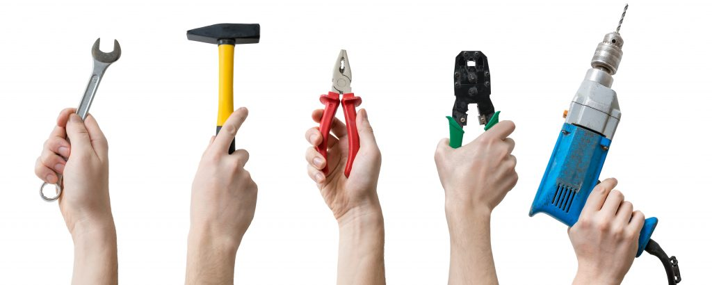 Many hands holds up instruments and tools. Isolated on white background. Maintenance concept.